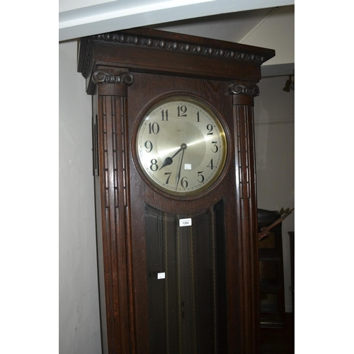 1384 - Oak longcase clock circa 1930, the rectangular case with flanking pilasters, the circular silvered d...