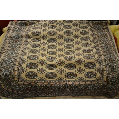 21 - Pakistan Bokhara design rug on beige ground, 239cms x 155cms...