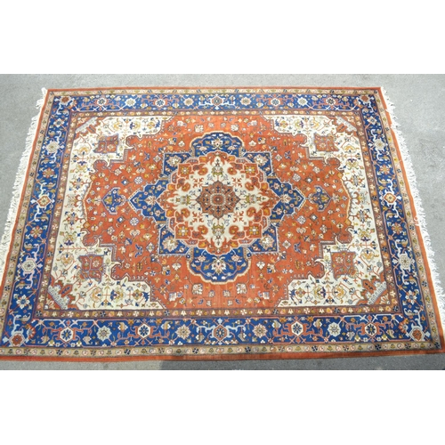 22 - Indo Persian carpet with a medallion and all-over floral design on a rust ground with borders...