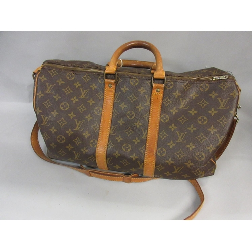 27 - Louis Vuitton holdall with tan leather trim together with a similar smaller holdall with shoulder st...