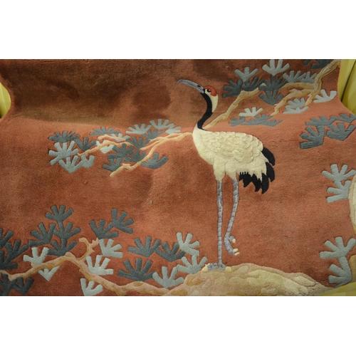 5 - Chinese woollen rug having bird decoration on a burgundy ground...