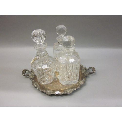 597 - Three various cut glass decanters with stoppers, together with a circular plated on copper two handl...