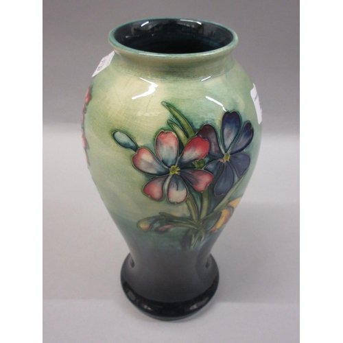 628 - Mid 20th Century Moorcroft baluster form vase with tubeline floral decoration, on a green and blue g...