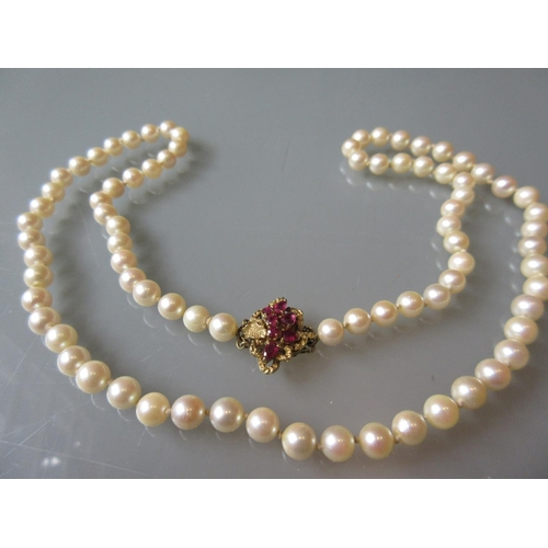 899 - Uniform cultured pearl necklace with a 14ct gold ruby set clasp...