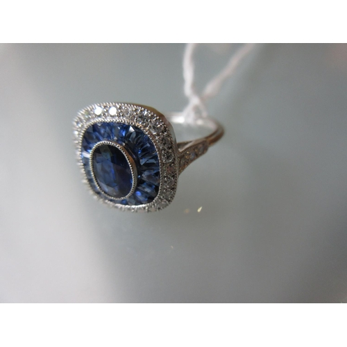 936 - Platinum ring set central sapphire and a halo of calibre cut sapphires and diamonds...
