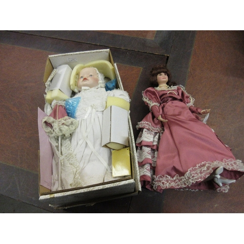 84 - Two modern bisque headed dolls together with a wooden dolls cradle...