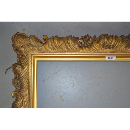 1068 - 19th Century gilded composition picture frame of rococo design, the aperture approximately 28ins x 2...