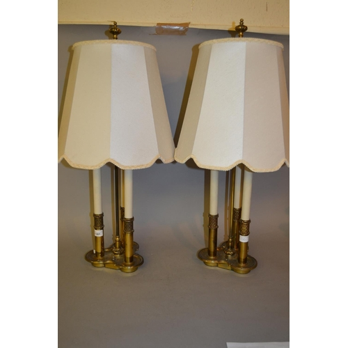 1381 - Pair of brass three light table lamps in the form of candles with matching shades, 30ins high...