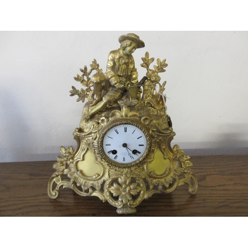 1511 - 19th Century gilt cased mantel clock surmounted with a figure fishing with circular enamel dial insc...