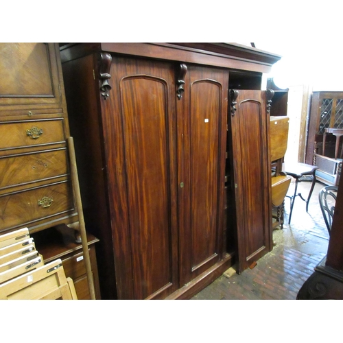 1531 - 19th Century mahogany three door wardrobe, the moulded cornice above long panel doors with carved de...