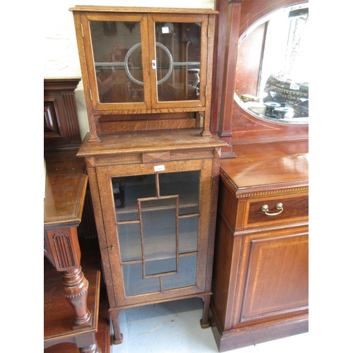 1581 - Oak Arts and Crafts style narrow bookcase with two leaded glazed doors above a single astragal glaze...
