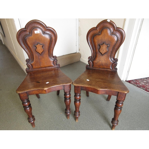 1593 - Pair of Victorian oak shield back hall chairs with panelled seats raised on turned front supports...