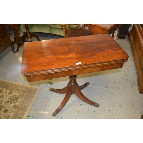 1599 - Reproduction mahogany rectangular fold-over card table on a turned column support and quadruped base...