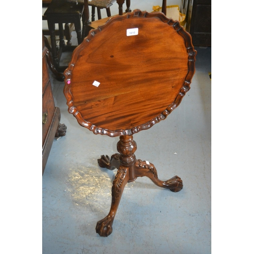 1610 - Reproduction mahogany wine table with a pie crust top, bird cage base and carved tripod...