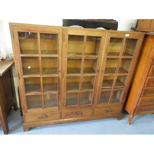 1949 - Mid 20th Century oak three door glazed bookcase with drawers below raised on bracket feet...