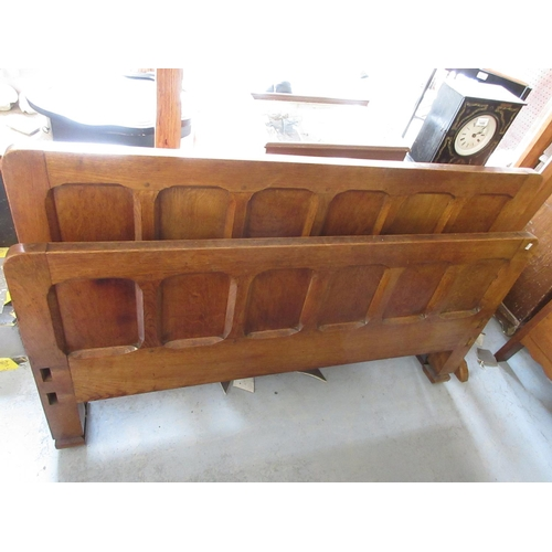 1950 - Arts and Crafts oak panelled bedstead together with a side cabinet having open shelves above two pan...