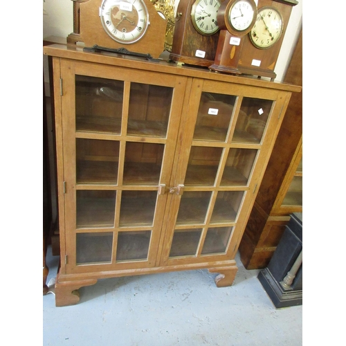 1953 - Pair of Arts and Crafts oak two door glazed bookcases on bracket feet...