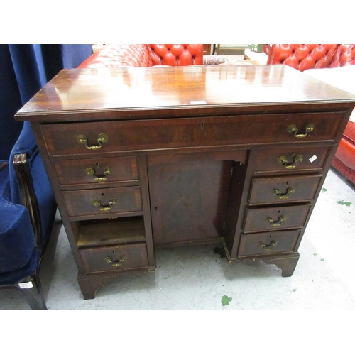 1984 - Reproduction mahogany and crossbanded kneehole desk with a long drawer above a cupboard door flanked...