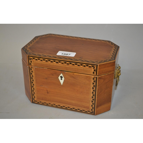 1987 - George III octagonal mahogany and inlaid tea caddy with lion mask ring handles...