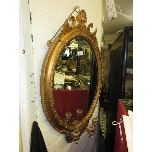 2010 - Oval gilt framed bevelled edge wall mirror with triple candle holder bracket...