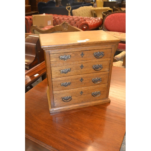 2026 - 19th Century oak table top collector's chest of four drawers with brass handles on a moulded plinth ...