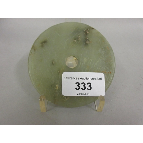 333 - Chinese carved pale green jade disc on a display stand...