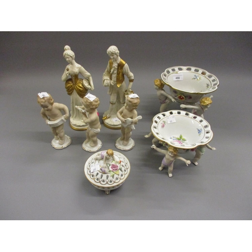 488 - Two Continental porcelain floral decorated dishes, each supported by standing figures, a similar box...