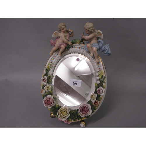 501 - Late 19th Century Continental porcelain oval table mirror mounted with roses and figures of cherubs,...