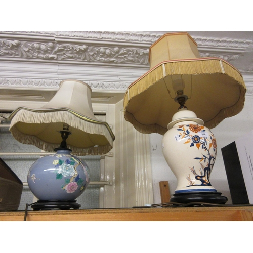 516 - Two Drimmer pottery floral and bird decorated table lamps on hardwood stands with shades...