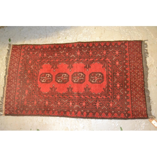 6 - Small rug having four central gols with multiple borders on a wine ground, 3ft x 1.5ft...