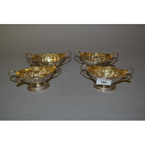704 - Set of four George III London silver two handled pedestal salts having embossed floral decoration, m...