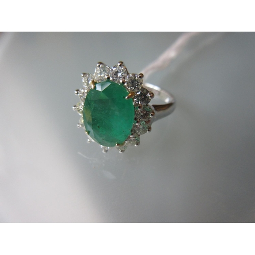 796 - 18ct White gold emerald and diamond cluster ring, the emerld approximately 3ct...