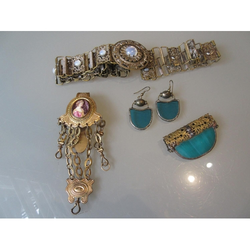 864 - Gilt metal chatelaine, moonstone inset belt, green glass panel brooch and a pair of similar earrings...