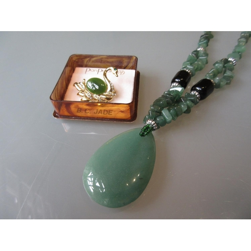 865 - Modern green jade pendant necklace together with a Canadian jade set brooch...