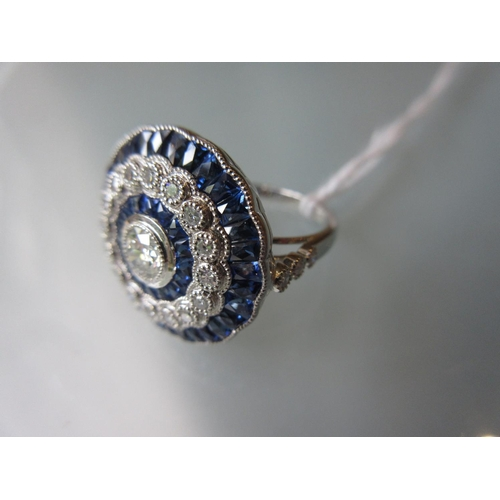 870 - Platinum ring set central diamond surrounded by calibre cut sapphires, a halo of diamonds and outer ...