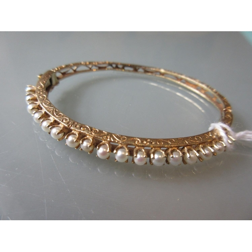 890 - Yellow gold pearl set bangle with safety clip (at fault)...