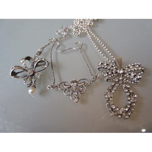 924 - Pair of silver necklaces together with a bow form paste set brooch...