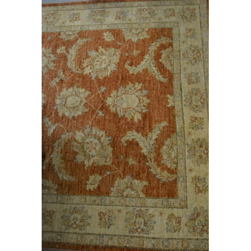 11 - Afghan Ziegler rug with an all-over floral design on a brick red ground, 69ins x 50ins...