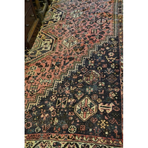 16 - Modern Shiraz carpet with central line of gols and multiple borders on a dark blue and red ground, 6...