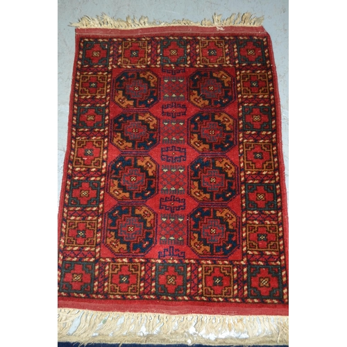 10 - Small Afghan rug with a repeating gol design on red ground, 71cms x 54cms...