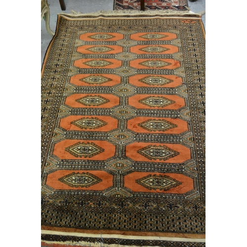 13A - Pakistan rug of Turkoman design with two rows of eight gols on rust ground...