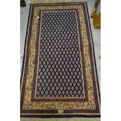 7 - Persian style rug of all-over Boteh design with multiple borders on blue ground with signature to th...