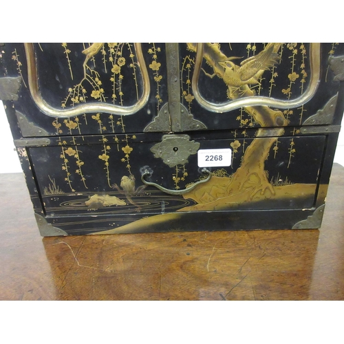 2268 - 19th Century Japanese black lacquered and gilt decorated table cabinet, the two doors opening to rev...