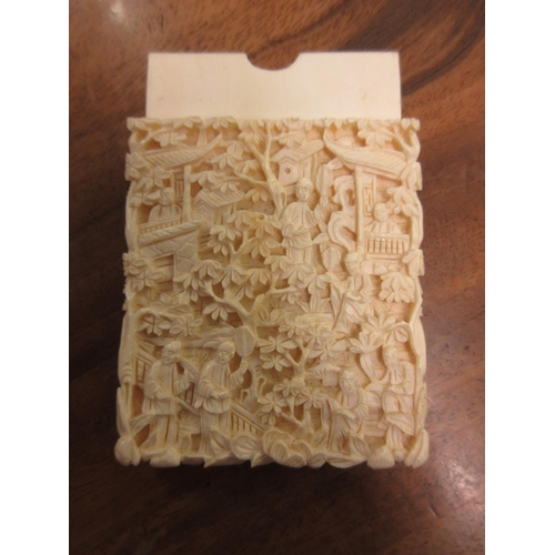 77 - 19th Century Chinese carved ivory card case decorated with figures in high relief, 4ins x 2ins appro...