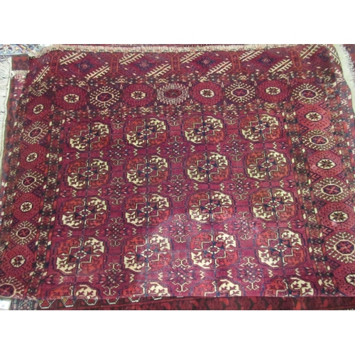 13 - Tekke rug with four rows of nine gols on a wine red ground with borders, 5ft 10ins x 3ft 10ins appro...