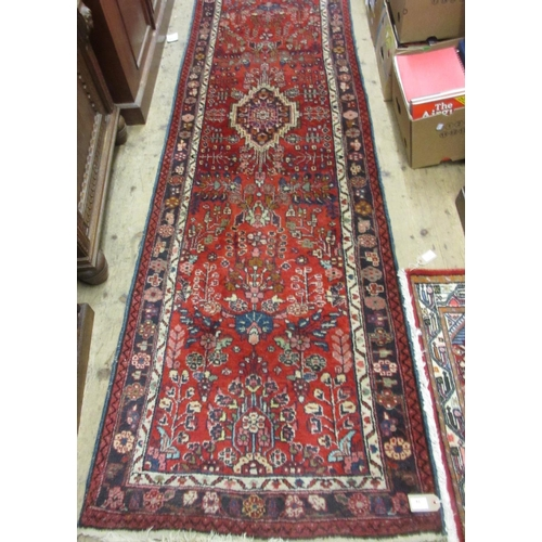 14 - Modern Saruq runner with a medallion and all-over stylised floral design on a red ground with border...