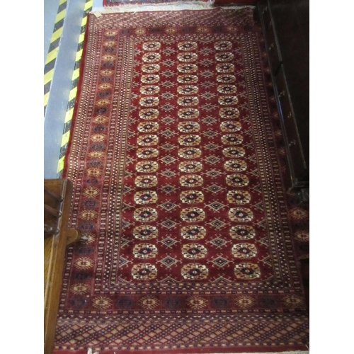 26 - Small Turkoman rug with two rows of gols on a red ground with borders, together with a similar large...