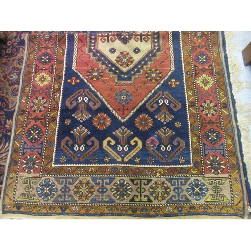 33 - Kurdish rug with medallion and all-over stylised design on a wine ground with borders...