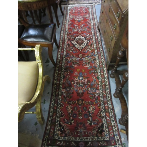 8 - Modern Saruq runner with a medallion and all-over stylised design on a red ground with borders, 10ft...