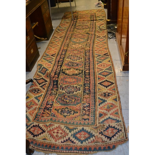 11 - Kurdish runner of hooked medallion design with borders, approximately 11ft 6in x 3ft (damages)...